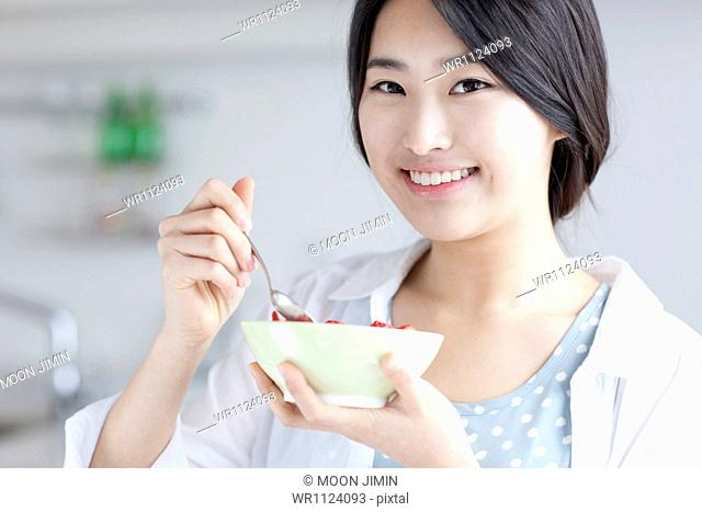 a young woman eating breakfast and working