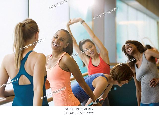 Smiling women talking and stretching in exercise class gym studio