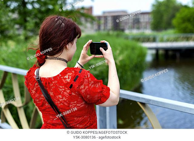 Bijlmer, Amsterdam, Netherlands. Young, redhaired woman making a Smart Mobile Photo with her Smartphone, when strolling through a city park on a Sunday...