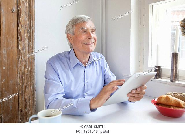 Thoughtful senior man looking away while holding digital tablet at table