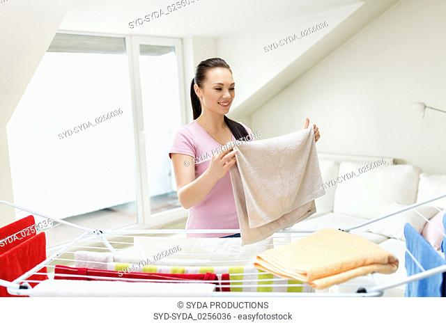 woman taking bath towels from drying rack at home