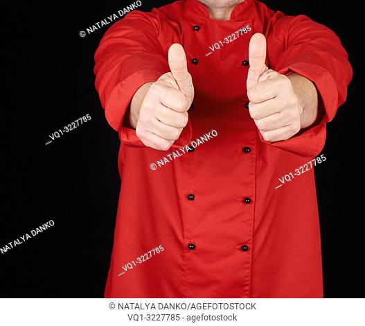 cook in red uniform stretched his arms forward and shows gesture like, black background, copy space