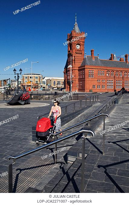 Wales, Cardiff, Cardiff Bay. A woman pushing a red pram along the waterfront of Cardiff Bay with the Pierhead building in the background