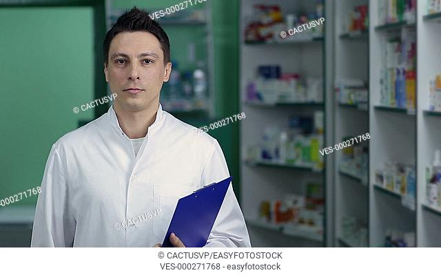 Smiling male pharmacist in white coat at drugstore