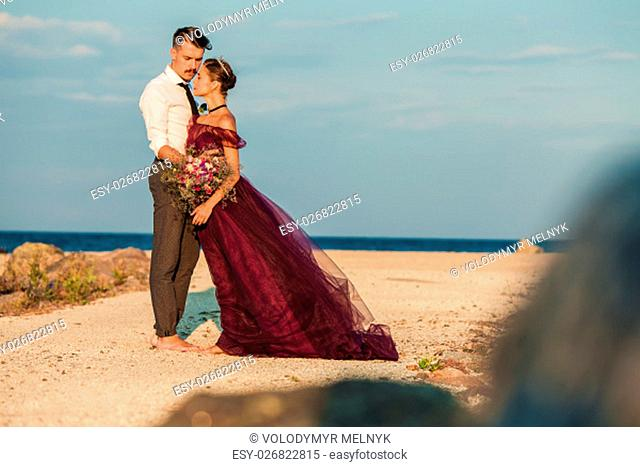 The wedding day at the sea. Young romantic couple relaxing on the beach watching the sunset