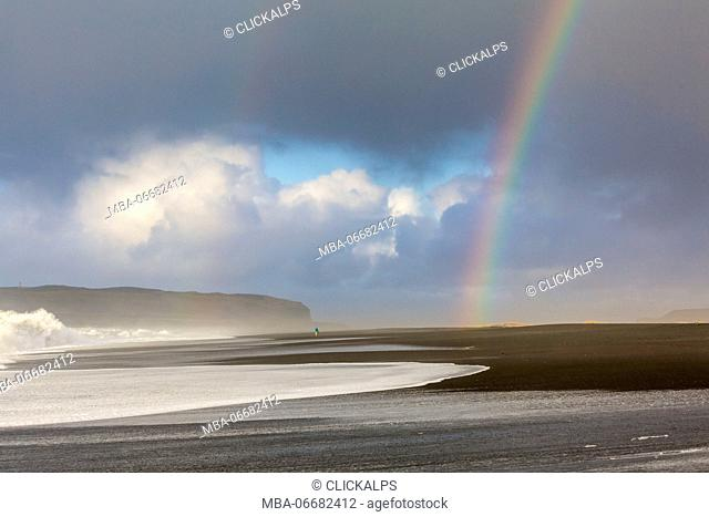 A man is walking towards the rainbow on the beach of Reynisfjara, Vik, Sudurland, Iceland, Europe
