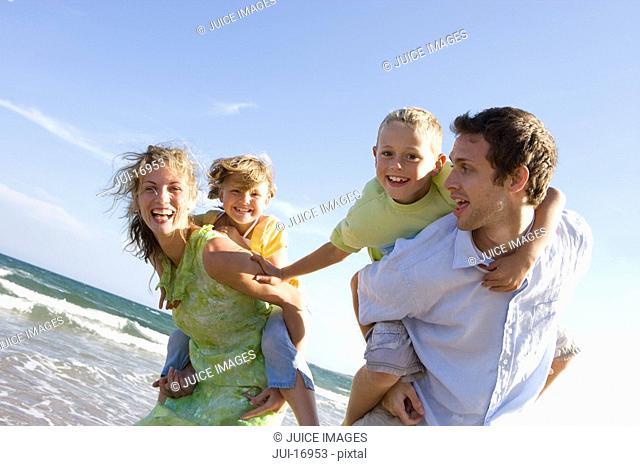 Parents piggybacking children on beach