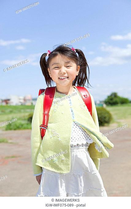 Japan, Tokyo Prefecture, Girl carrying school bag, smiling, portrait