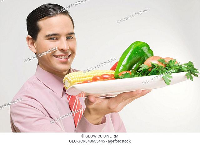 Businessman holding a platter of fresh vegetables