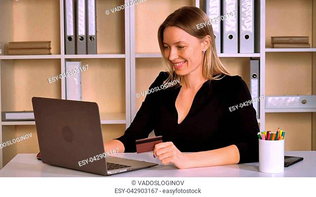 busy business woman shopping online sitting at the desk in modern office. attractive worker with blonde hair using internet make payment