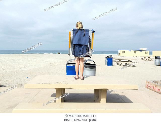 Caucasian girl carrying folding chair on picnic table at beach