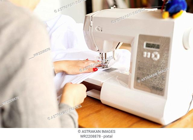 Midsection of design professional using sewing machine at table