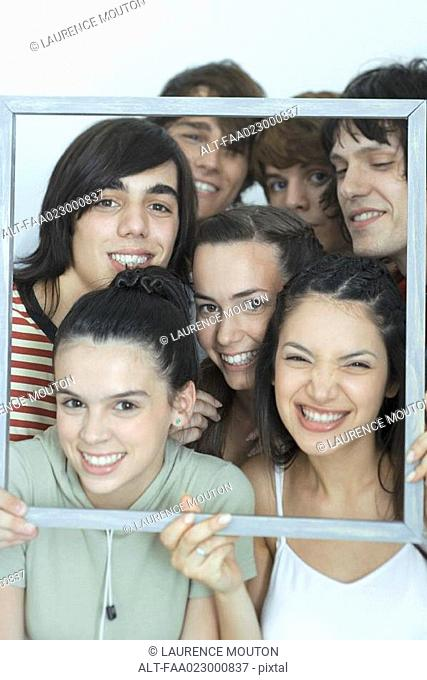 Group of young friends posing for photo, holding up picture frame, smiling at camera, portrait