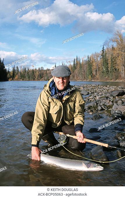 Angler with steelhead, Bulkley river, British Columbia, Canada