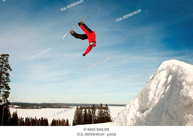 Mid adult male snowboarder upside down during mid air jump