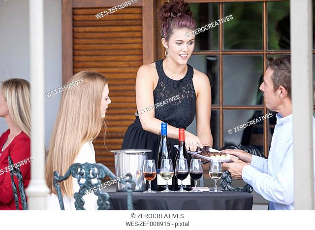 Waitress serving wine and chocolates in restaurant