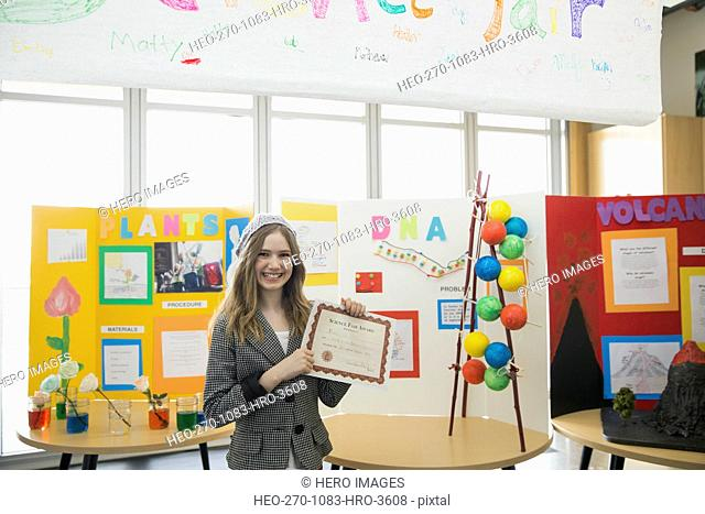 Portrait of school girl with award at science fair
