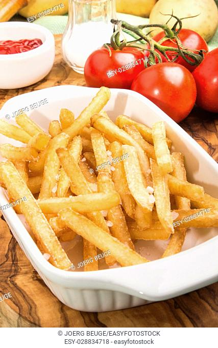 golden brown french fries in a white bowl with tomato, salt and ketchup