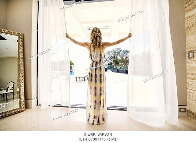 Rear view of woman looking out of bedroom window