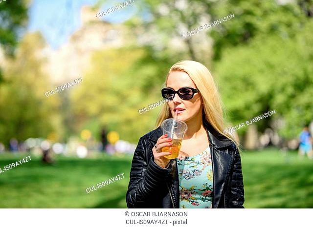 Female tourist having takeaway drink in Central Park, New York, USA