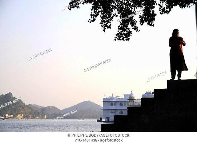 India, Rajasthan, Udaipur, City palace and Pichola lake, woman cleaning laundry