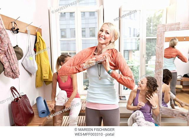 Woman putting on her clothes in yoga studio changing room