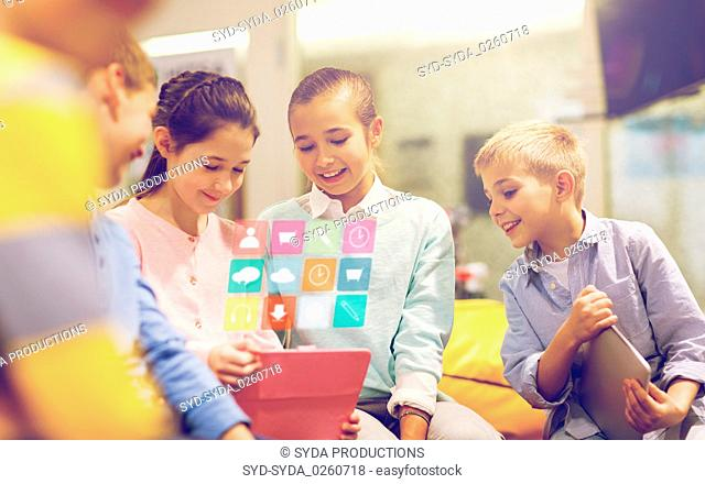 group of happy children with tablet pc at school
