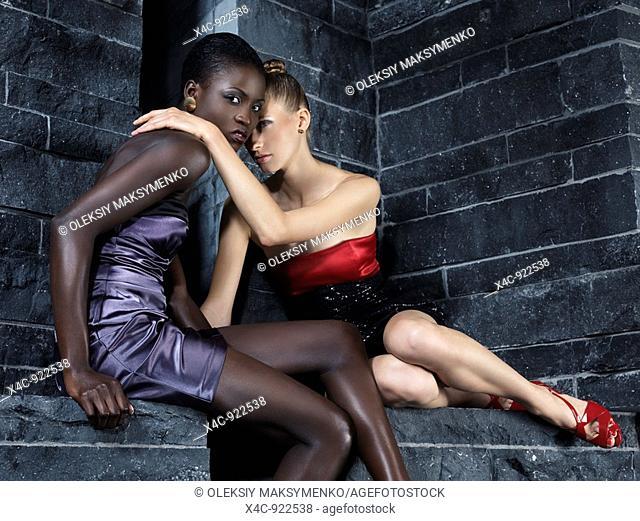Two beautiful women in elegant dresses sitting on a stone wall High fashion