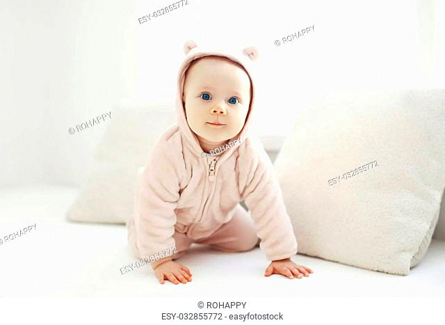 Portrait of cute baby at home in white room