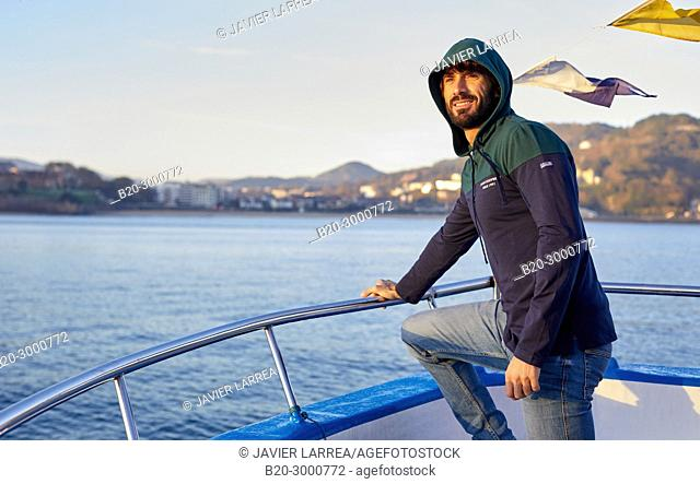 Adult man in a tourist boat to Santa Clara Island, Donostia, San Sebastian, Gipuzkoa, Basque Country, Spain, Europe, Winter