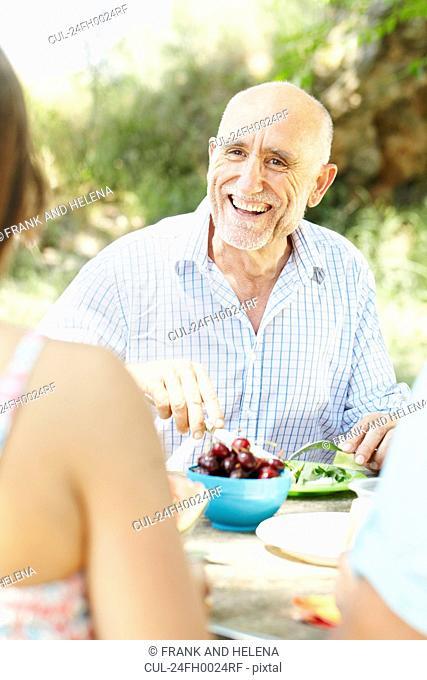 Smiling older man at picnic table