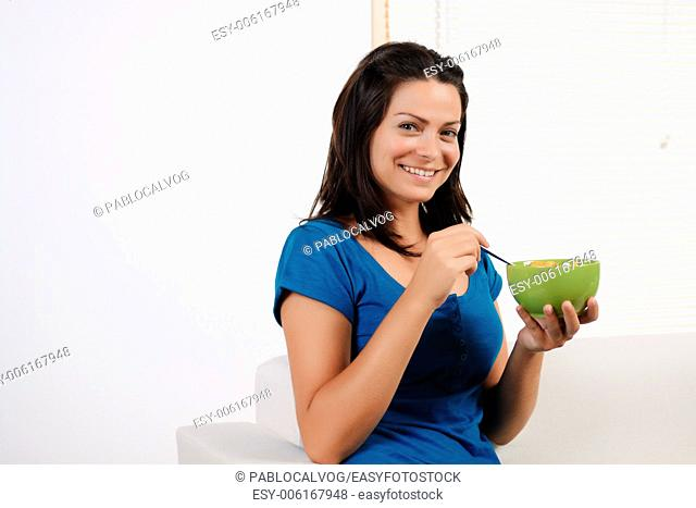 Portrait of a beautiful young woman having breakfast cereal while smiling at the camera