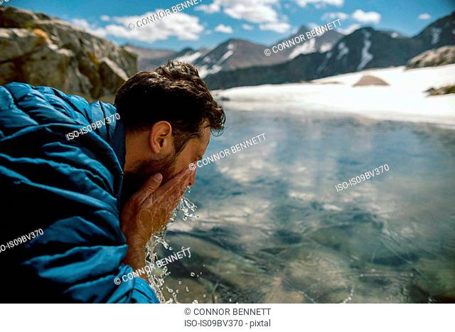 Hiker freshening up at lake, Mineral King, California, United States