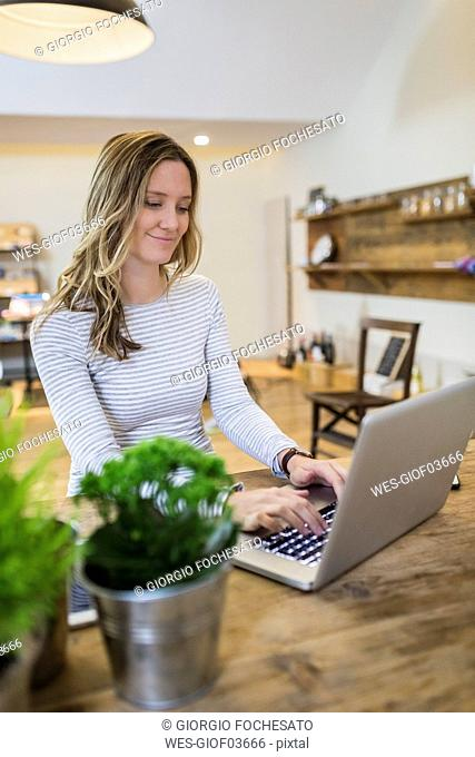 Smiling woman using laptop on wooden table at home