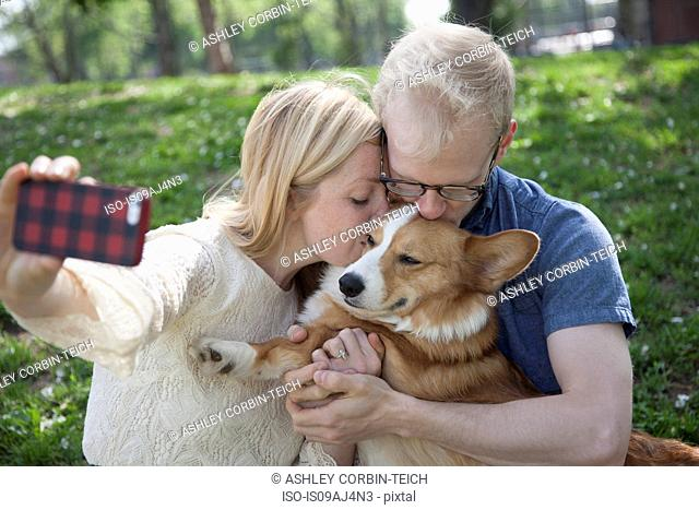 Young couple in park taking selfie whilst kissing corgi dog