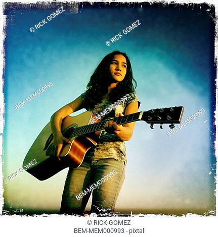 Hispanic girl playing guitar outdoors