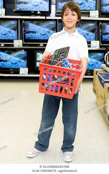 Boy carrying a shopping basket in a supermarket