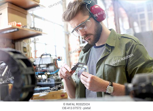 Male designer using caliper in workshop