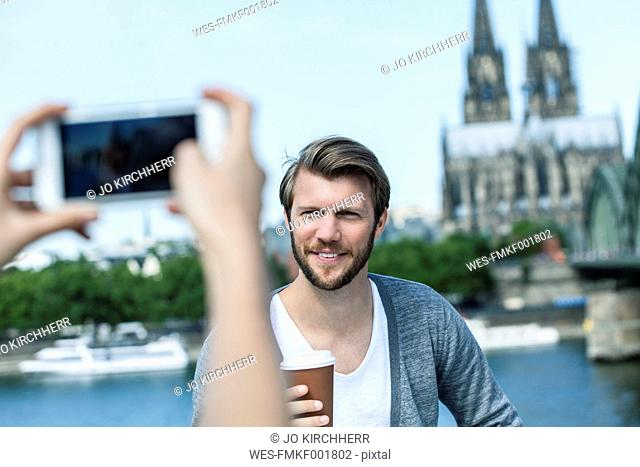 Germany, Cologne, young woman taking a picture of her boyfriend with smartphone