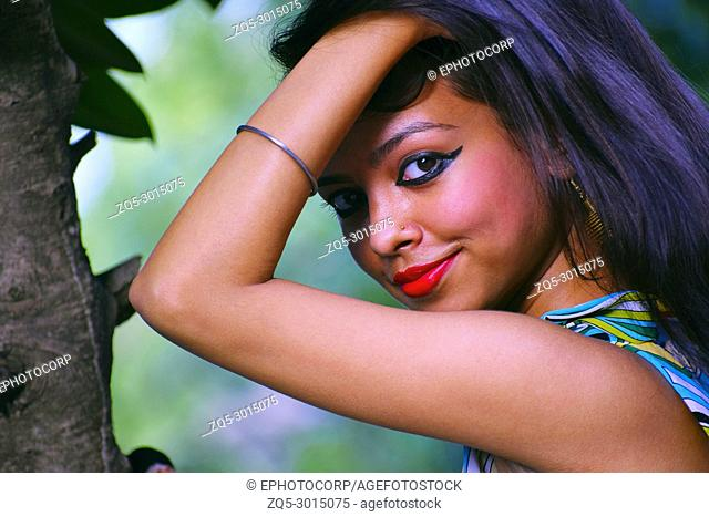 Young girl looking at camera with tree in , Maharashtra