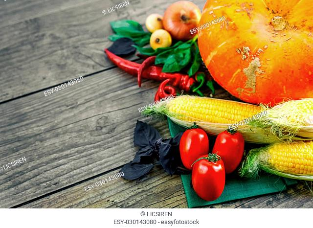 Fresh vegetables on a dark table. Autumn background. Healthy eating. Pumpkin, bell peppers, paprika, tomatoes,basil, corn cob Top view