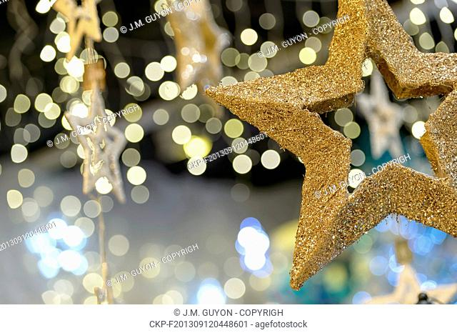 Metallic gold star Christmas ornament on shimmering blurred background