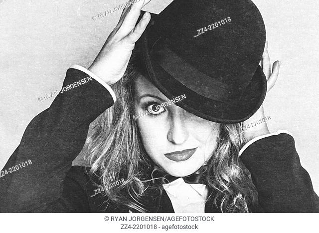 Rough textured image of a broadway entertainer holding vintage hat while looking at camera in a depiction of a cabaret theatre show
