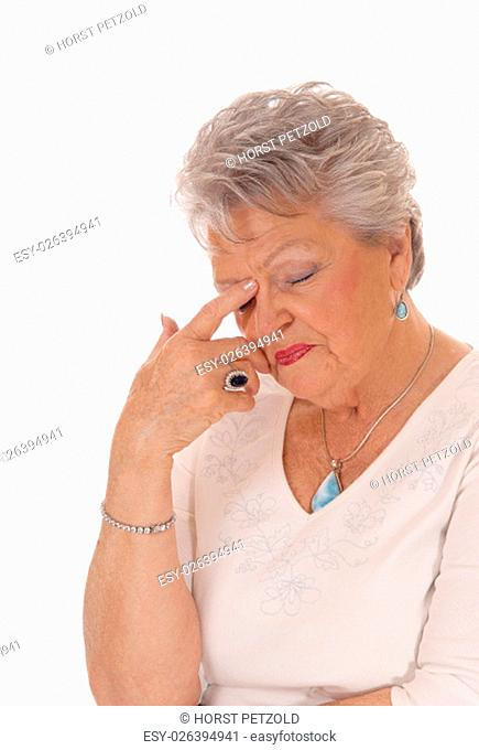 A closeup image of a very sad looking senior citizen woman in her seventies .with short grey hair isolated for white background.