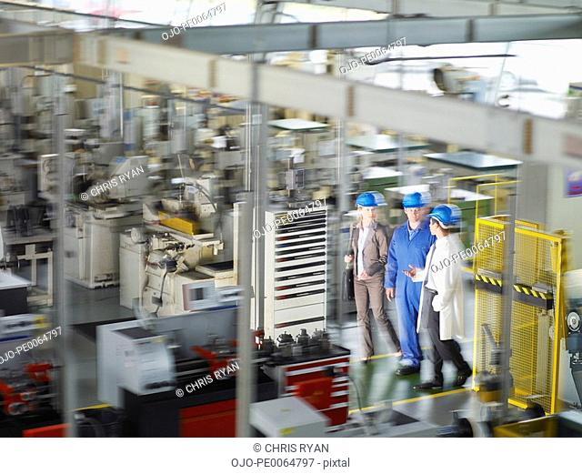 Businesspeople in hard-hats walking on factory floor