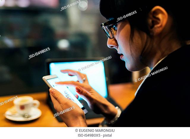 Businesswoman using mobile phone and laptop in cafe