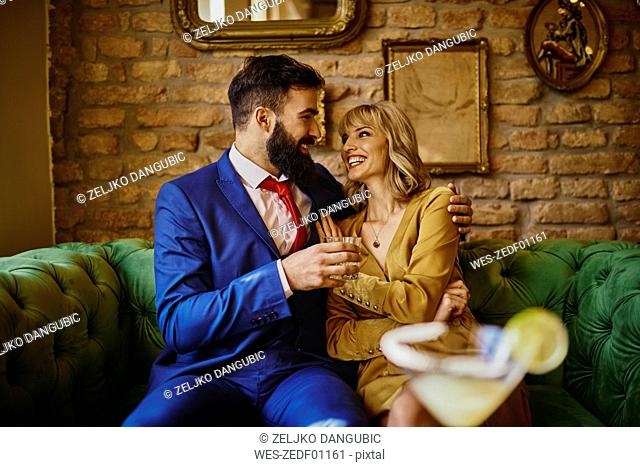 Happy elegant couple sitting on couch embracing
