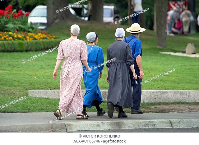 Mennonite girls with father walking on a street in Niagara Falls, Ontario, Canada