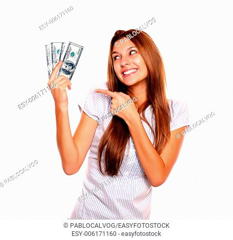 Portrait of a smiling young woman with long brown hair looking and pointing to cash money on isolated background