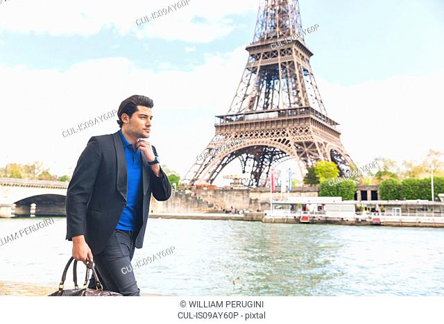 Young man walking beside river, Eiffel Tower in background